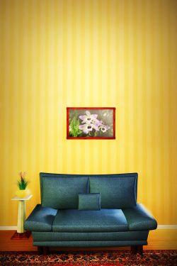 Salon z czarnym, skórzanym fotelem i obrazem z kwiatami na tle ściany z żółtą tapetą - sxc.hu by dleafy