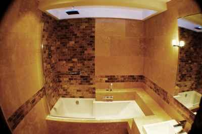 Łazienka, w której na pierwszym tle widzimy wannę, obok również umywalka, w oczy rzucają się brązowe, doskonale komponujące się z pomieszczeniem płytki - source: FLICKR.com by Ken Doerr