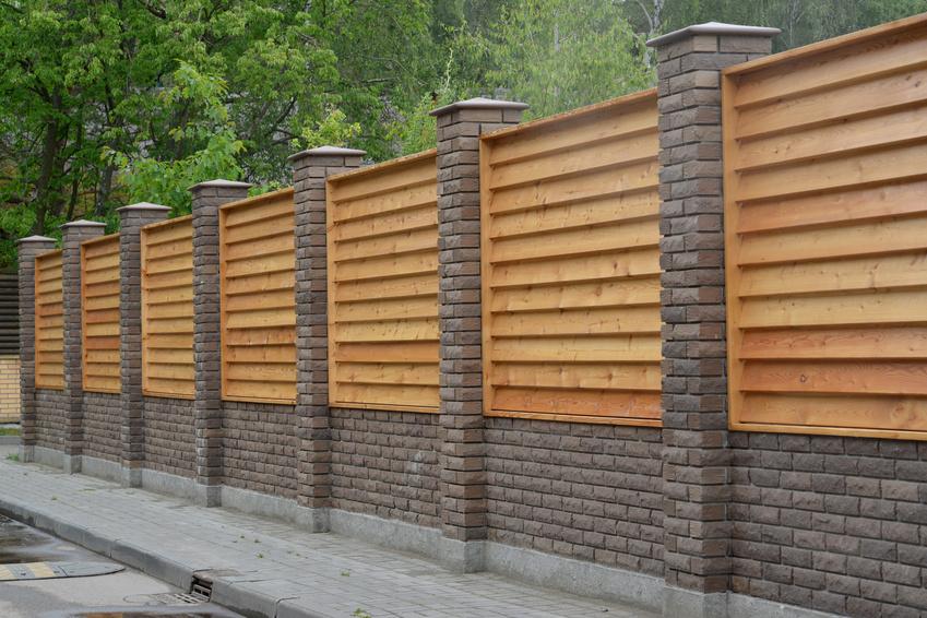 Ogrodzenie ozdobne składające się z cegły klinkierorwej i paneli drewnianych