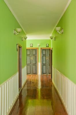 Przedpokój ze ścianami pomalowanymi na zielono, drewniana, lakierowana podłoga, ciemne, dwuskrzydłowe drzwi i kinkiety - freedigitalphotos.net By gubgib