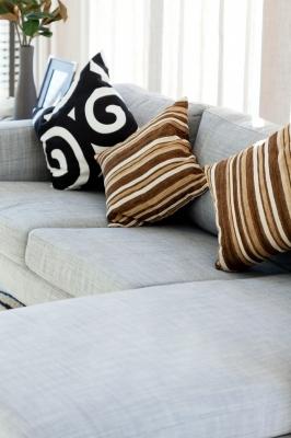 Szara sofa z trzema poduszkami w różnych kolorach - source: FreeDigitalPhotos.net By jackthumm