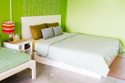 Sypialnia urządzona na zielono, ściany z interesującymi wzorami, delikatnie zielona narzuta , na podłodze panale i dywan -  freedigitalphotos.net By Phiseksit