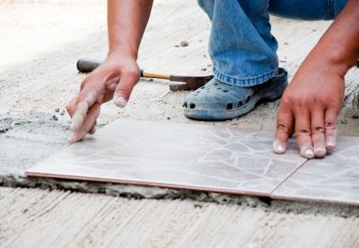 Glazurnik kładzie kolejną płytkę na przygotowaną wcześniej zaprawę klejową - souce: FreeDigitalPhotos.net - by sixninepixels