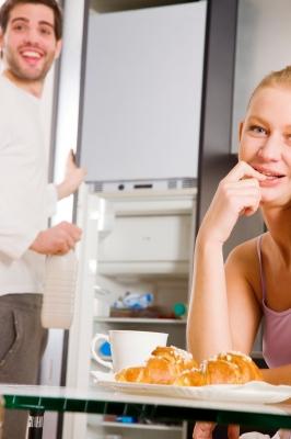 Para siedzi w kuchni, facet trzyma drzwi lodówki, oboje się śmieją - source: FreeDigitalPhotos.net By Ambro