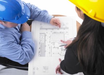 Dwójka budowlańców pochyla się nad planem budynku - source: FreeDigitalPhotos.net By adamr
