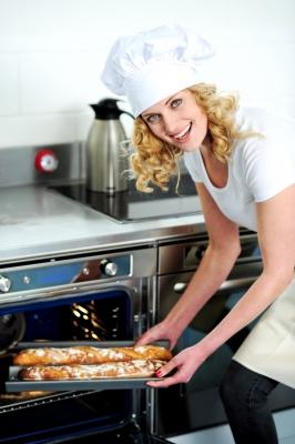 Kobieta w kuchni, wyciąga z piekarnika ścieżo upieczone bagietki - source: FreeDigitalPhotos.net By stockimages