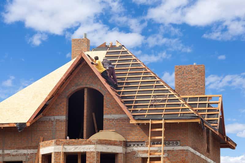Mężczyźni pracujący podczas budowy dachu oraz dach jętkowy jako jedno z możliwych rozwiązań