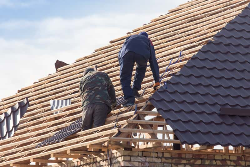 Mężczyźni podczas prac przy budowe dachu. Dach krokwiowo-jętkowy podczas wykańczania konstrukcji.