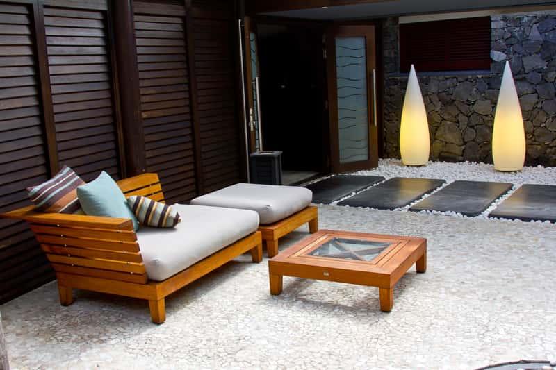 Gustowny drewniany komplet mebli ogrodowych z Ikei lub Castoramy. Uroku dodają mu jasne pokrowce na meble ogrodowe.