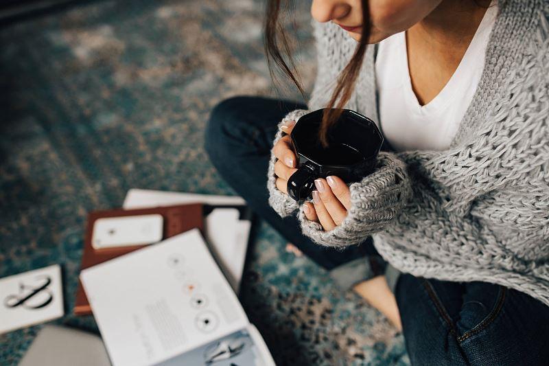 Dziewczyna czyta gazetę i pije kawę