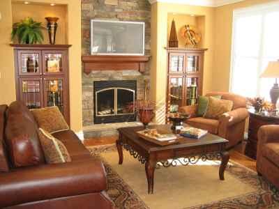 Salon urządzony w stylu brytyjskim, dominują brązowe barwy, po lewej skórzana kanapa, po prawej dwa fotele i stolik kawowy na środku, na drugim tle widać kominek ponad którym znajduje się płaski TV