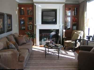 Kolejny przykład salonu, w którym nad kominkiem umieszczono telewizor, tym razem odbiornik TV znajduje się w specjalnie przygotowanej wnęce, w salonie poza kominkiem znajdują się dwa regały na książi, zamszowa sofa, dwa fotele z różnych kolekcji oraz szklany stolik kawowy. Na podłodze pasiasty dywan
