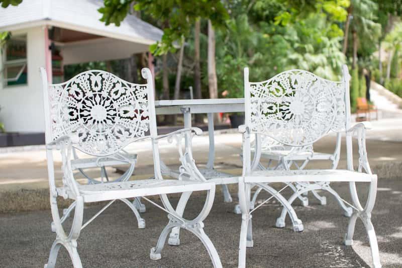 Meble ogrodowe aluminiowe, w których na pierwszy plan wysuwają się dwa białe krzesła aluminiowe.