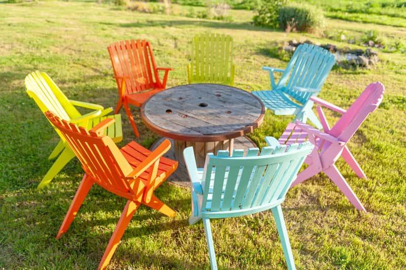 Kolorowe krzesła plastikowe wokół stołu jako meble ogrodowe dla osób ceniących tanie rozwiązania.