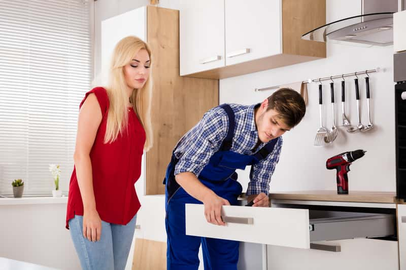 Mężczyzna podczas montażu mebli kuchennych