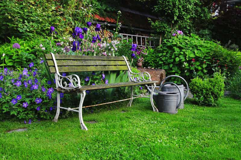 Metalowa ławka ogrodowa z drewnianym siedziskiem jako inspiracja na ławki ogrodowe do ogródka