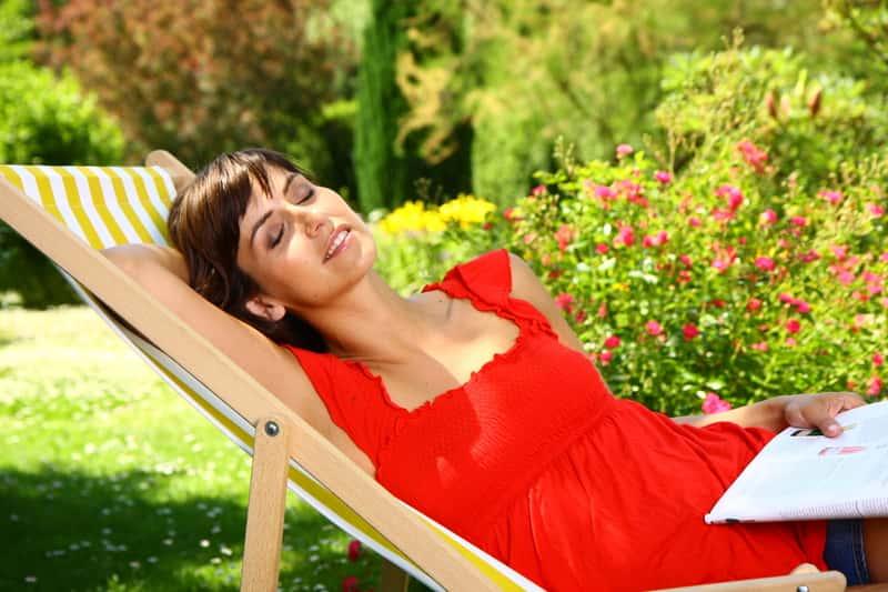 Kobieta leżąca na leżaku ogrodowym, wśród których popularne są leżaki plastikowe, aluminiowe czy drewniane