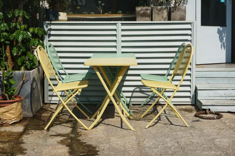 Żółte i zielone meble aluminiowe przy aluminiowym stole. Komplet mebli ogrodowych idealnych dla każdego.