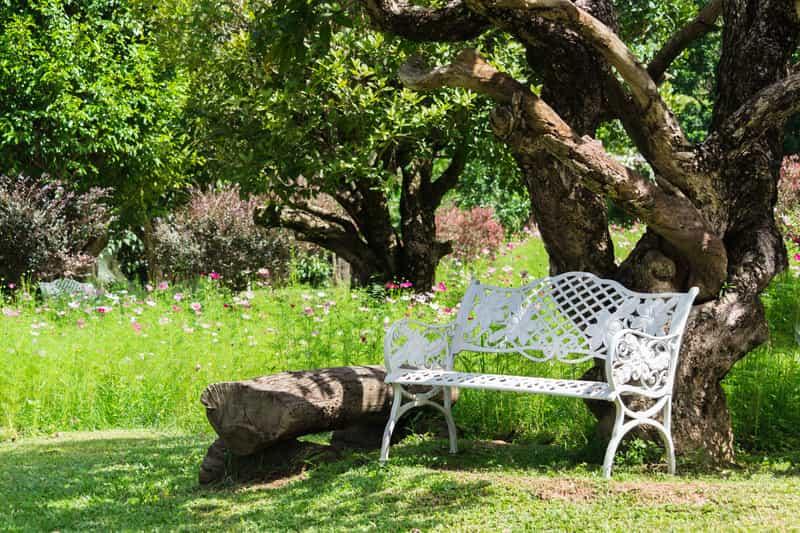 Metalowa ławka ogrodowa jako element kompletu mebli ogrodowych z metalu w kolorze białym