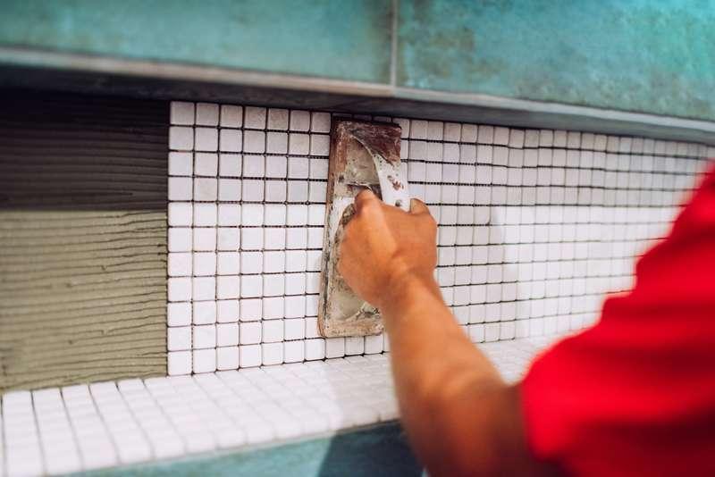 Prace podczas układania mozaiki na ścianie