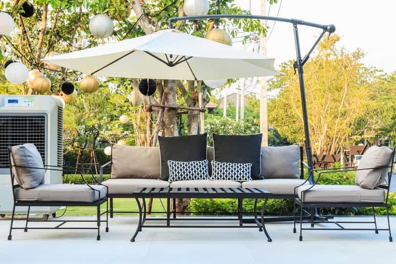 Nowoczesne meble ogrodowe, czyli nowoczesne krzesła i nowoczesne stoły z otwartym parasolem nad nimi