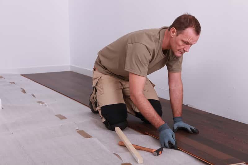 Mężczyzna układający panele podłogowe