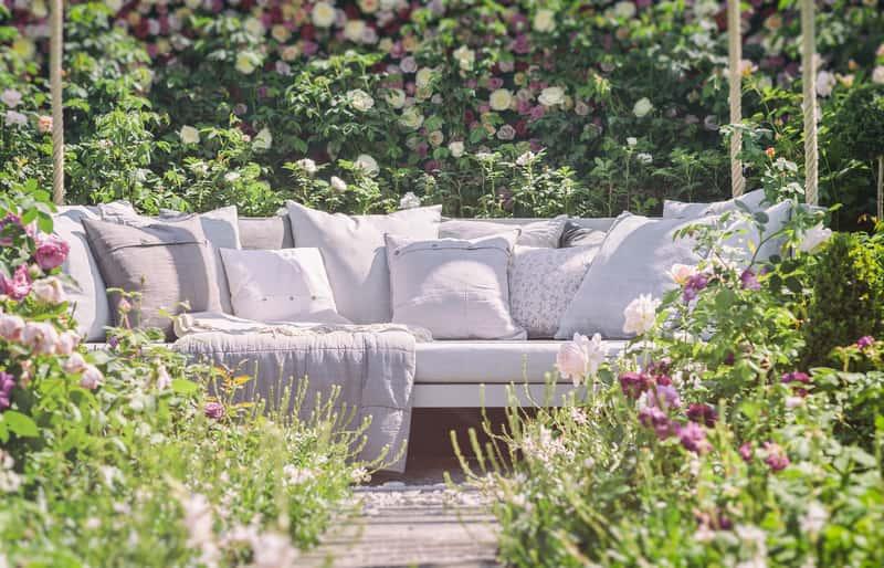 Jasne poduszki ogrodowe na meble ogrodowe w postaci tapiecerowanej ławki idealnej na taras lub balkon