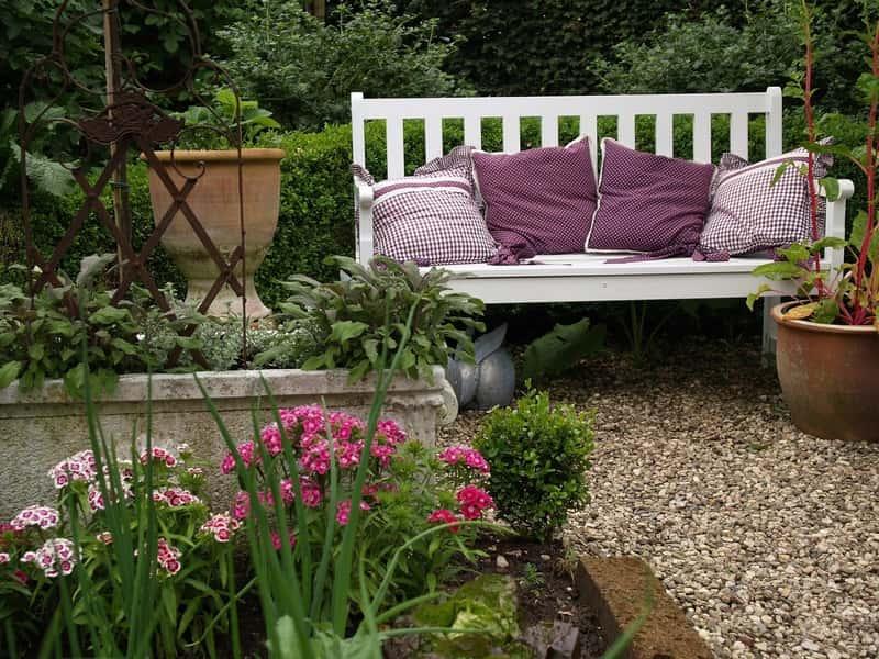 Dekoracyjne poduszki ogrodowe na różnego rodzaju meble ogrodowe, na przykład w postaci białej ławki ogrodowej