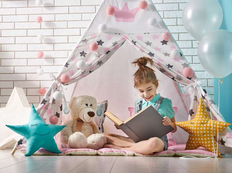 Dziewczynka z książką w pokoju dziecięcym