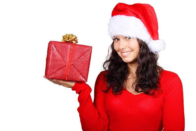 Piękna kobieta w przebraniu Mikołaja z prezentem w ręki