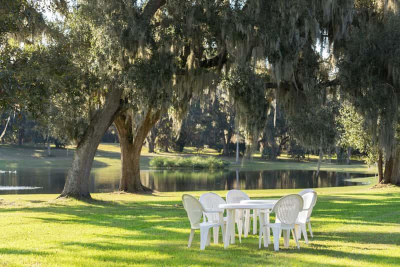 Biały stół plastikowy z krzesłami na trawie jako inspiracja na stoły ogrodowe do przydomowej przestrzeni