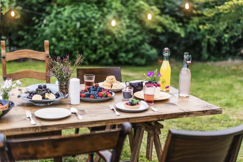 Bogato nakryty stół ogrodowy rozkładany drewniany jako przykład na stoły ogrodowe na podwórku czy działce