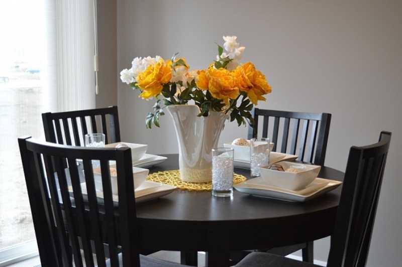 Stolik ozdobiony ciekawym wazonem z białymi i pomarańczowymi kwiatami