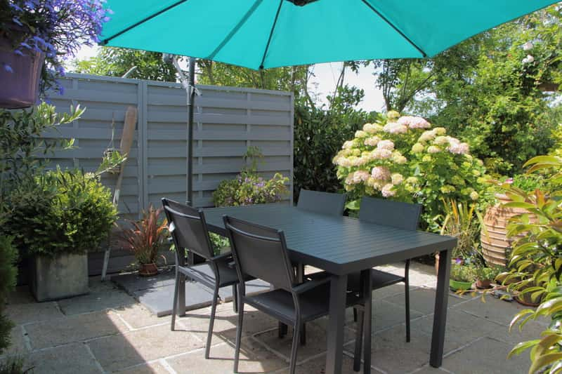 gotowy zestaw mebli ogrodowych z IKEI lub z Castoramy pod zielonym parasolem ogrodowym na podwórku