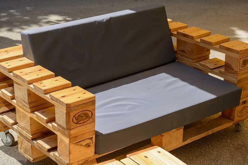 Kanapa z palet wyłożona ciemną poduszką, a także meble ogrodowe zrobione z palet, projekty, inspiracje i wykonanie