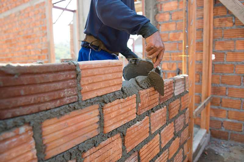 Budowanie niewysokiego murku z cegły dziurawki połączonej zaprawą murarską, a także ceny, waga oraz zastosowanie cegły dziurawki