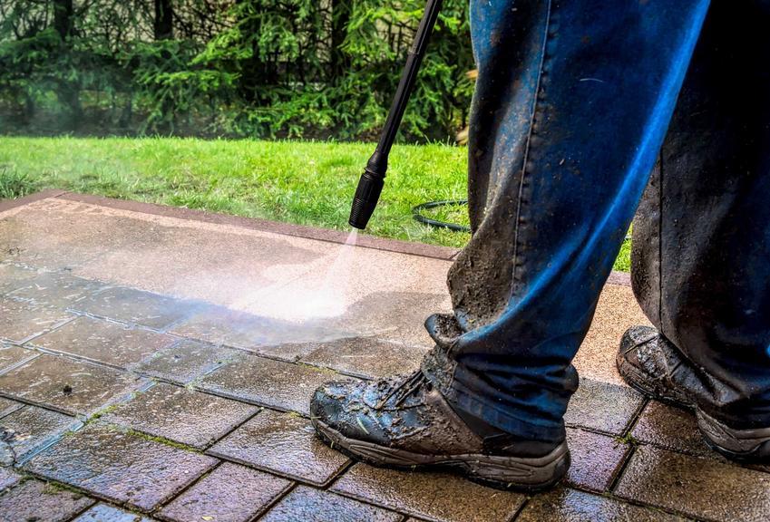 Mycie kostki brukowej myjką pod wysokim ciśnieniem przez mężczyznę w stroju roboczym i ubłoconych butach