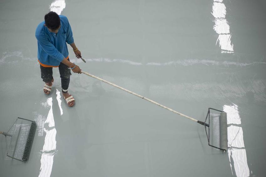 Zakładanie podłogi z żywicy przez specjalistę zacierającego mechanicznie nierówności na szarej, błyszczącej podłodze odbijającej światło świetlówek