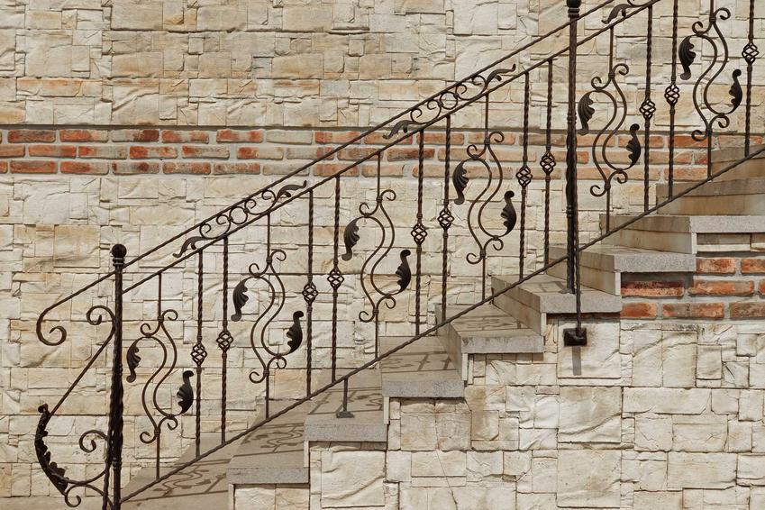 Schody kamienne wykończone ładną, kutą balustradą, która bardzo atrakcyjnie wygląda. Ceny takiego rozwiązania mogą być jednak dość wysokie.