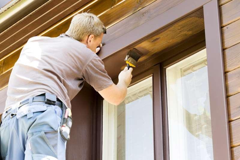 Mężczyzna dokonujący samodzielnej renowacji okna drewnianego i malujący je brązową farbą krok po kroku, czyli naprawa i odnowienie okien