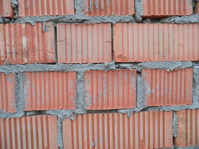 Czerwone cegły z zaprawą murarską, a także inne rodzaje cegieł: silikatowa, pełna, kratówka, zastosowanie, wady, zalety i opis
