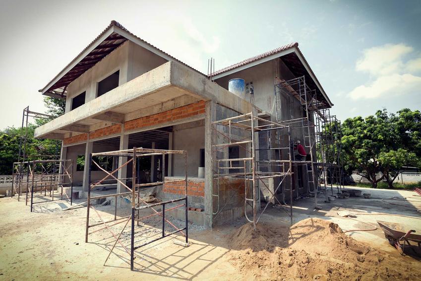 Budowa domu jednorodzinnego z szarego pustaka, szkielet domu bez okien i drzwi, bez elewacji z ustawionymi rusztowaniami