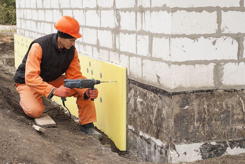Zakładanie izolacji fundamentów i osuszanie fundamentów poprzez wiercenie kanalików przeprowadzane przez robotnika ubranego w strój roboczy z wiertarką