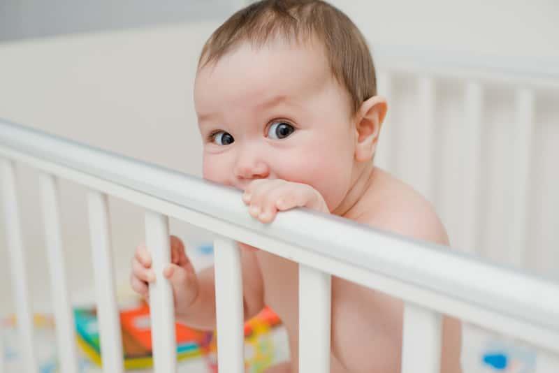 Małe dziecko w łóżeczku, a także najważniejsze rzeczy podczas wyboru łóżeczka dziecięcego, ceny, rodzaje, atesty