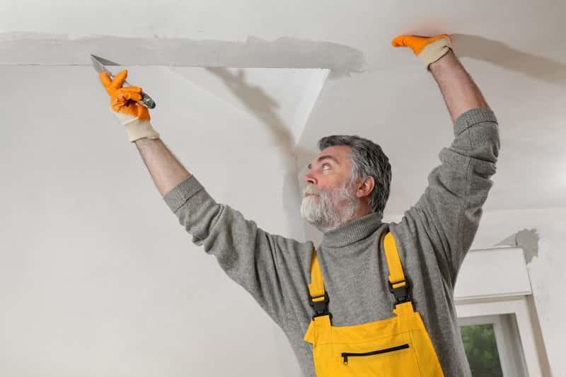 Mężczyzna przygotowujący sufit napinany, a także montaż sufitu, rodzaje, zastosowanie, wielkość i sposoby na przygotowanie sufitu