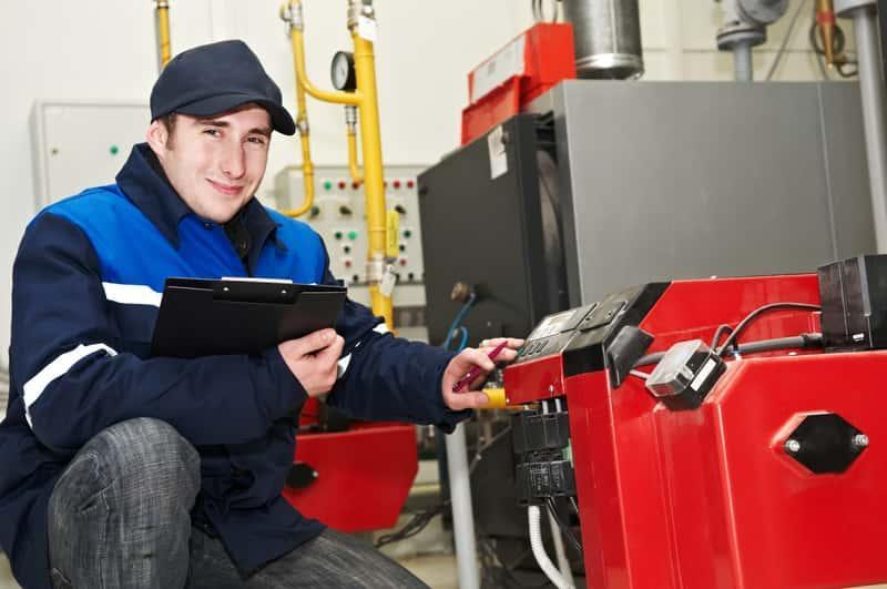 Mężczyzna przeprowadzający montaż pieca centralnego ogrzewania, a także montaż instalacji CO krok po kroku w domu jednorodzinnym