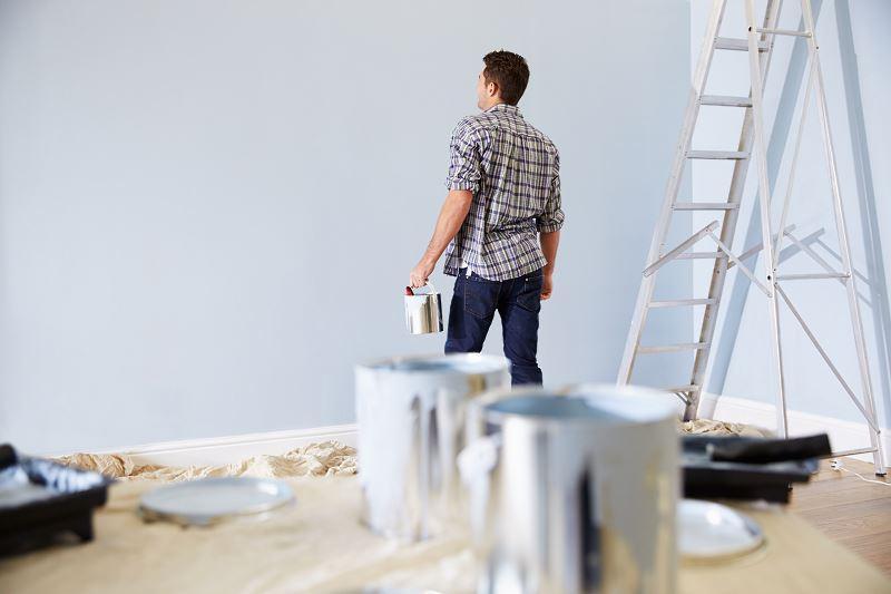 Robotnik maluje ściany w wykańczanym domu w budynku w stanie surowym zamniętym podczas prac wykończeniowych