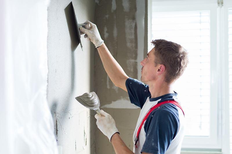 Tynkowanie ścian - robotnik tynkuje ściany podczas prac wykończeniowych w domu w stanie surowym zamkniętym.
