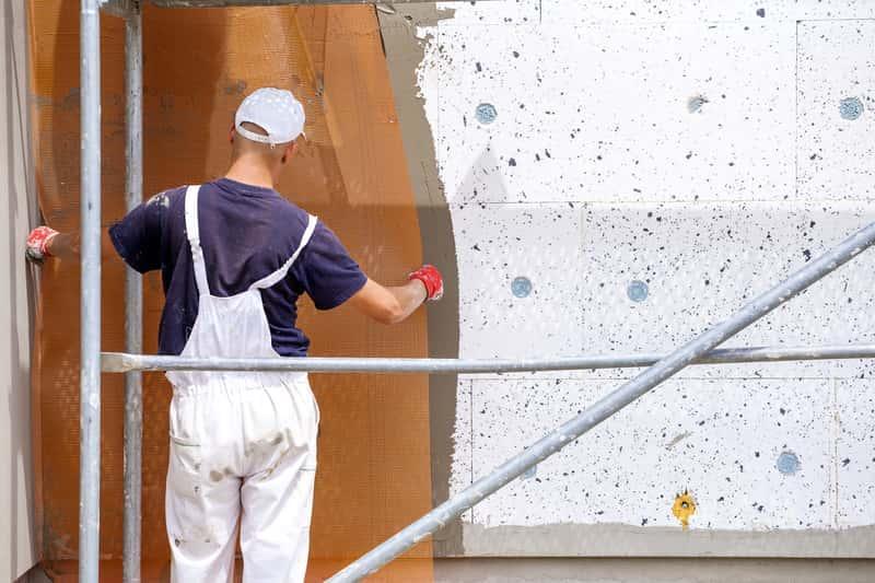 Mężczyzna w stroju roboczym kładący siatkę elewacyjną na klej, a także informacje o klejach do zatapiania siatki elewacyjnej i polecani producenci