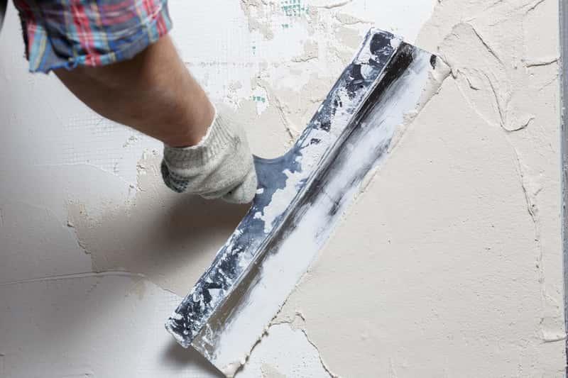 Mężczyzna kładący gładź gipsową na ścianach, a także rodzaje, sposoby kładzenia gładzi, ceny produktów oraz zastosowanie